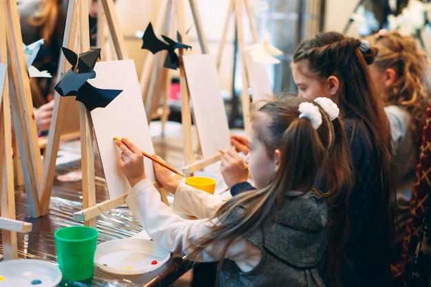 描画中のグループレッスン。子供たちは教室で絵を描くことを学びます。