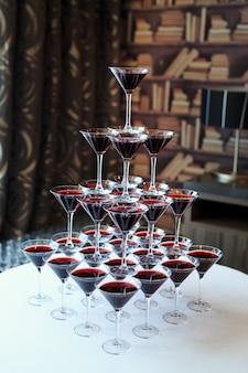 Официант наливая красное вино или шампанское в бокалы для вечеринки.