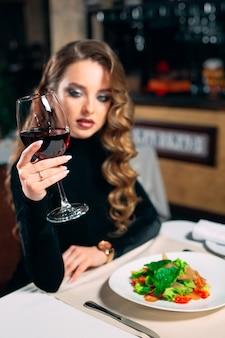 レストランでワインを飲む若い美しい女性。