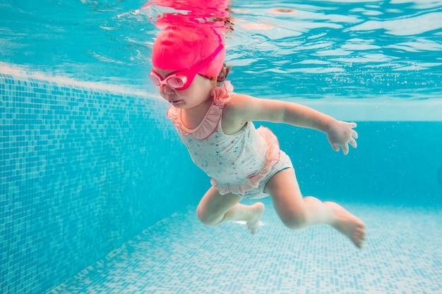Ребенок. счастливый малыш учится плавать, нырять под водой и веселиться в бассейне, чтобы поддерживать себя в форме. подводное плавание.