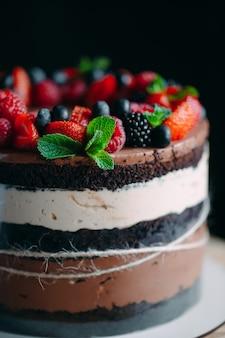 Фруктовый торт торт украшенный ягодами на деревянной подставке на черном