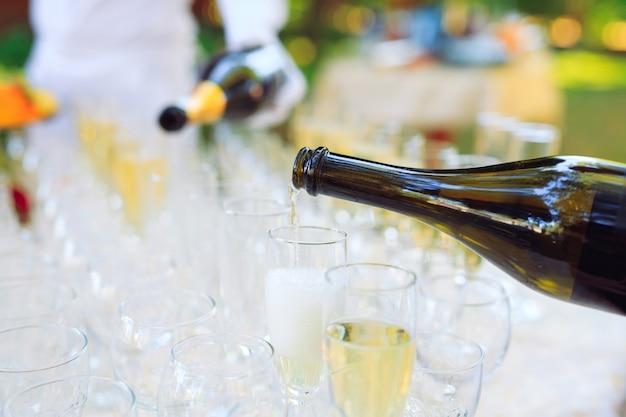 グラスにシャンパンを注ぐバーテンダー