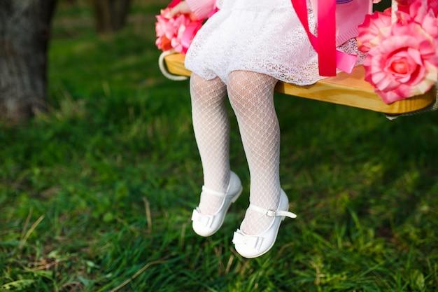 Маленькая девочка верхом на качелях. ноги заделывают на зеленой траве.