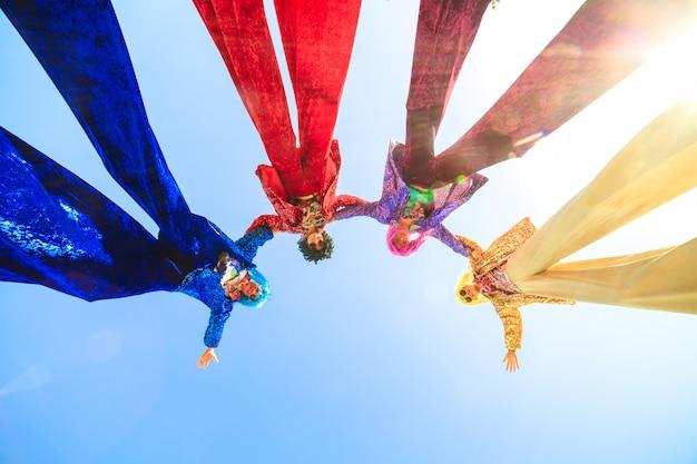 Молодые люди на ходулях, позируя на фоне голубого неба.