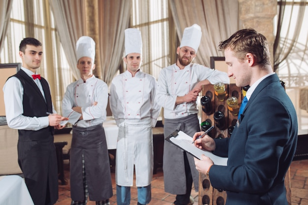 Менеджер ресторана и его сотрудники на кухне. общение с шеф-поваром на коммерческой кухне.