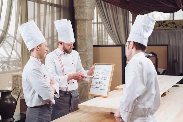 Шеф-повар и его сотрудники на кухне. взаимодействовать на коммерческой кухне.