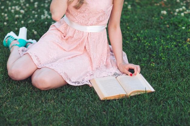Маленькая девочка сидя на траве и читая книгу.