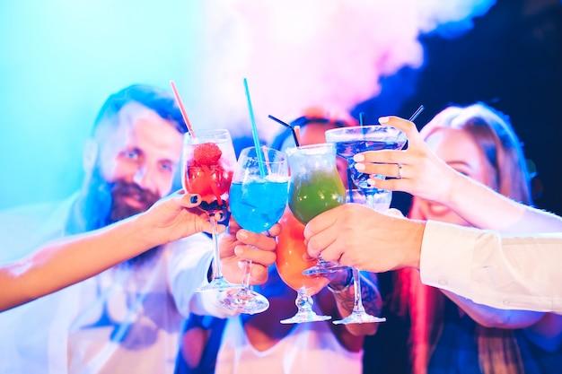 カクテルを飲みながら友達がパーティーで飲みます。