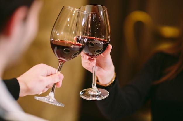 男と女が赤ワインを飲みます。写真では、眼鏡をかけた手のクローズアップ。