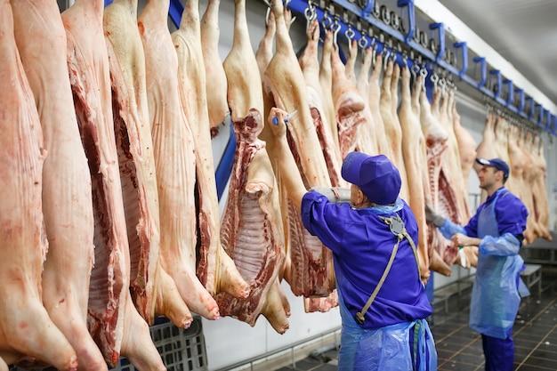 肉屋で肉屋の豚肉をカットします。