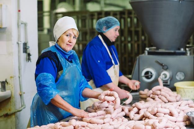肉屋は肉工場でソーセージを処理します。