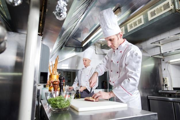 まな板で肉を切るシェフ、ナイフを保持しているプロの料理人、レストランで肉を切る