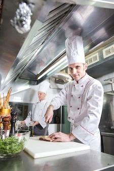 Шеф-повар режет мясо на разделочной доске, профессиональный повар держит нож и нарезает мясо в ресторане