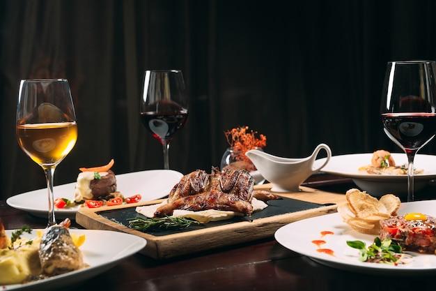 ヤマウズラ焼き、スズキ、タルタルス。レストランのテーブルにさまざまな料理。