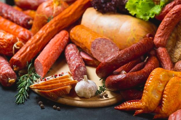 Различные виды колбас и мясных продуктов на черном.