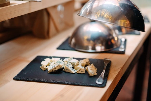 Нарезка сыра на металлическую чашу с крышкой. завтрак в отеле или ресторане.