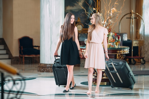 Молодые девушки возле стойки регистрации в отеле, молодые девушки приходят в отель.
