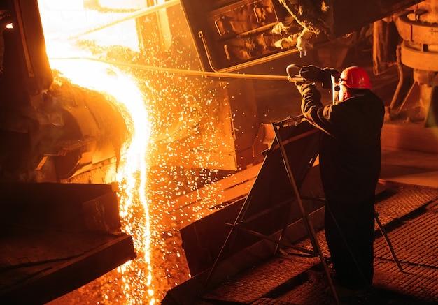 Завод по производству стали. электроплавильная печь. фабричный рабочий берет образец на металл.