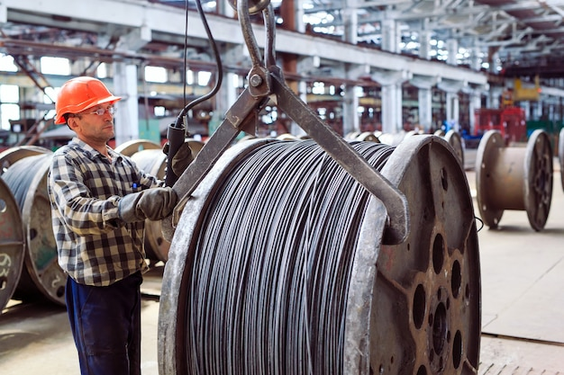 ワイヤーロッド、倉庫のフィッティング。カタコイとバンドルと一緒に労働者。冶金工場の工業用倉庫。