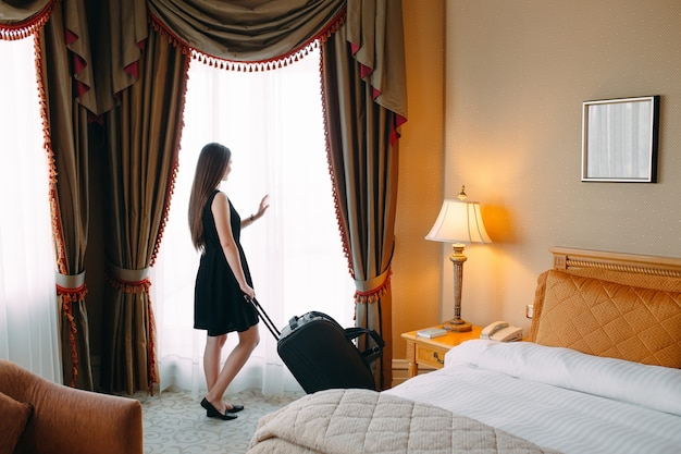 スーツケースを持つ若い女性はホテルの部屋に滞在しています。