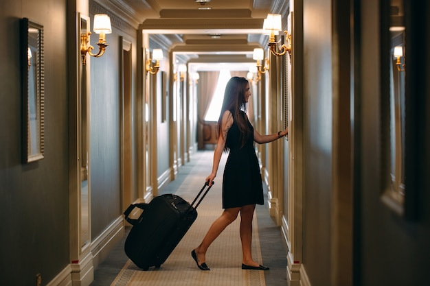 ハンドバッグとエレガントなスーツのスーツケースを持つ若い女性は、彼女の部屋にホテルの廊下を歩きます。