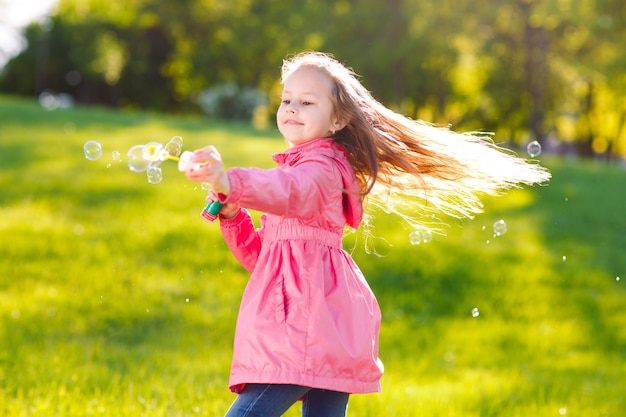 シャボン玉で遊ぶ女の子。