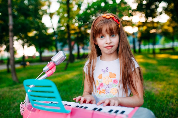 少女が公園でおもちゃのピアノで遊んで