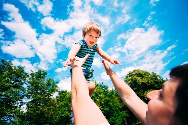 Молодой отец и сын, играя в парке.
