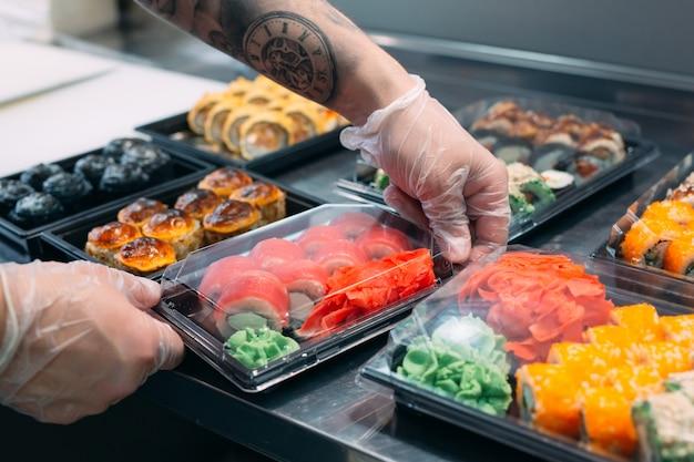 寿司配達。プラスチック製の箱に入ったさまざまな種類の寿司が配達用に準備されています。