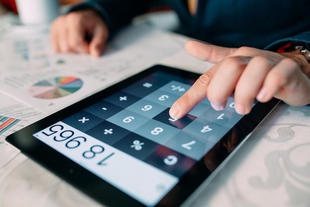 Конец-вверх руки предпринимателя анализируя счет на цифровом планшете над столом,