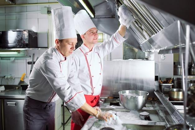 Санитарный день в ресторане. повара моют духовку, плиту и вытяжку в ресторане.