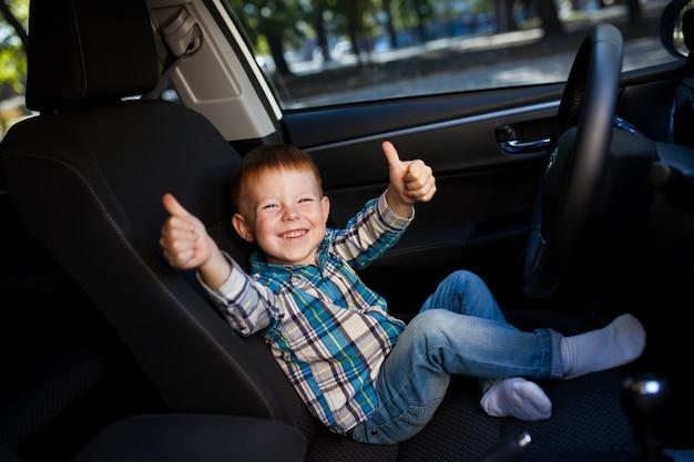 Милый маленький мальчик за рулем автомобиля отцов