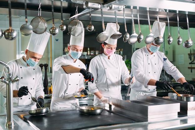 Повара в защитных масках и перчатках готовят еду на кухне ресторана или отеля.