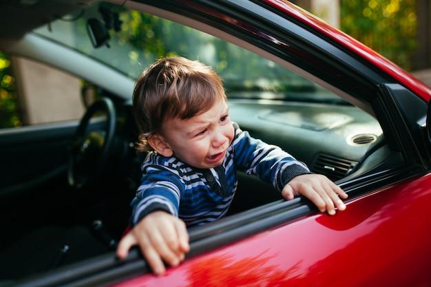 車で泣いている男の子。