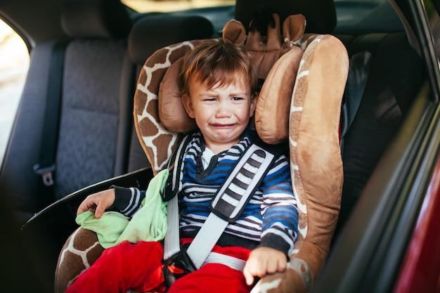 車の座席で泣いている男の子。