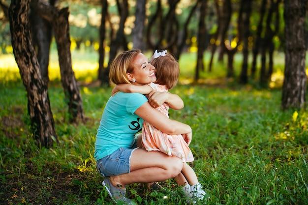 Счастливая мама и дочь, улыбаясь на природе.