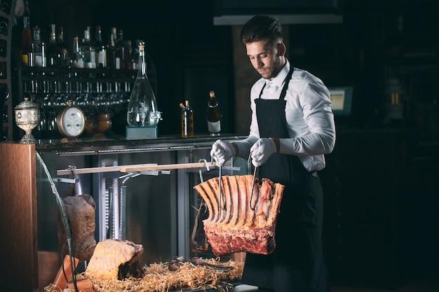 Официант или повар получает сухое мясо в холодильнике.