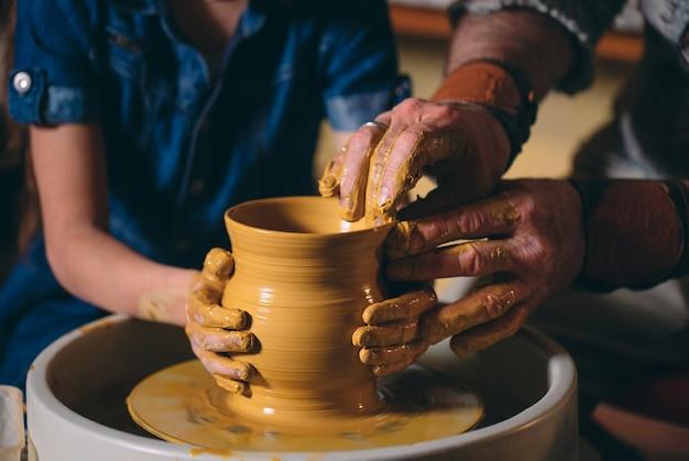 陶芸ワークショップおじいちゃんは孫娘の陶器を教えています。粘土モデリング