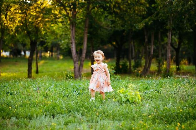 Счастливая милая маленькая девочка бежать на траве в парке. счастье
