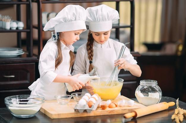面白い女の子の子供たちは台所で生地を準備しています。