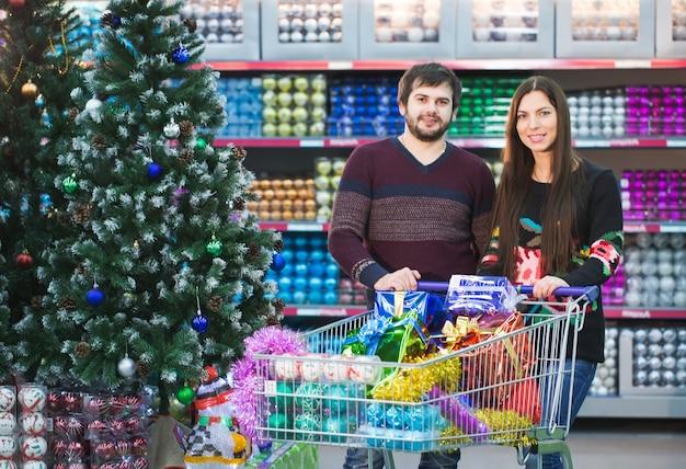 Молодая пара делает покупки в супермаркете на новый год.