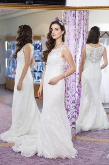 お店でウェディングドレスを試着する女性。