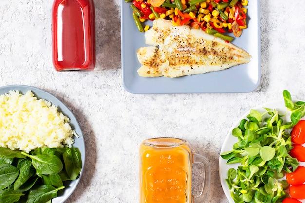 Здоровый обед концепция здорового питания. запеченная рыба, рис, свежий шпинат, салат, помидоры черри, запеченные свежие овощи