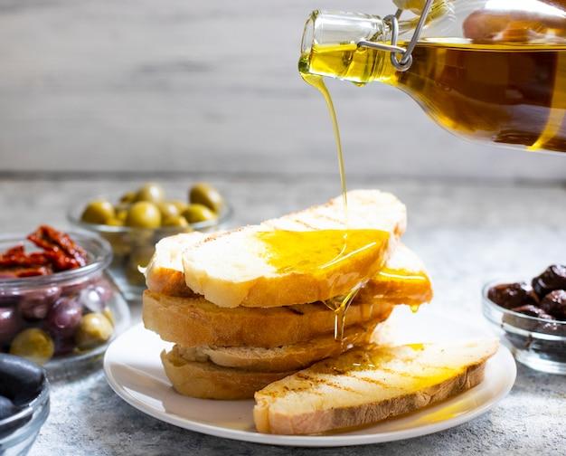 Лить оливковое масло из стеклянной бутылки на брускетты, миску оливок и вяленых помидоров. крупный план