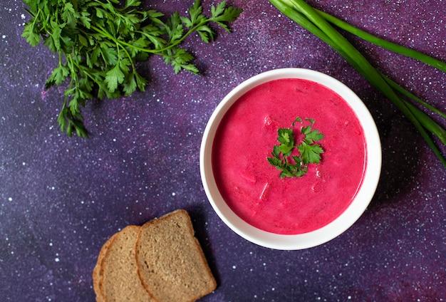 冷たいクリーミーなビートルートスープ、ビートルートガスパチョパンと新鮮なハーブの白い皿で提供しています。明るい紫色の背景。ベジタリアン、クリーンな食事のコンセプト。コピースペース。上面図