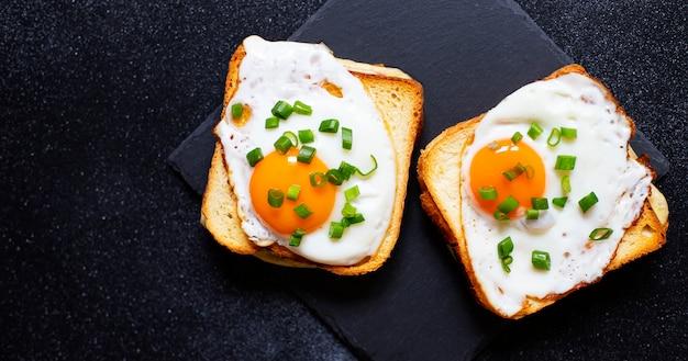 ハム、チーズ、卵のサンドイッチ。黒いプレートにレタスの葉を添えた伝統的なフランスのクロックマダムサンドイッチ。人気のフレンチカフェのお食事。黒の背景。上面図。テキストのためのスペース
