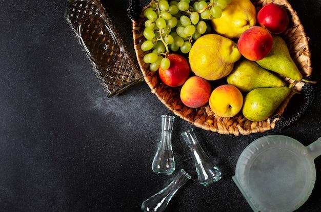 Ракия или ракия - традиционный балканский фруктовый бренди. плоды которых производят ракия. фрукты в корзине, бутылки и стаканы для алкоголя. вид сверху. черный фон. пространство для текста