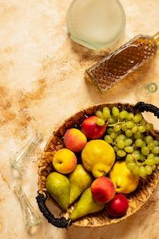 Ракия или ракия - традиционный балканский фруктовый бренди. плоды которых производят ракия. фрукты в корзине, бутылки и стаканы для алкоголя. вид сверху. легкий старинный фон. пространство для текста
