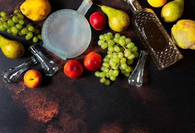 Ракия или ракия - традиционный балканский фруктовый бренди. плоды которых производят ракия. фрукты, бутылки и стаканы для алкоголя. вид сверху. темный старинный фон. пространство для текста