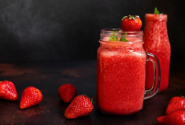 イチゴのスムージーや氷を入れたイチゴ。さわやかな夏の飲み物。黒の背景。正面図。コピースペース
